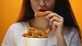 Meisje die kippenvleugels, hoog calorievoedsel en gezondheidsrisico's, cholesterol eten stock videobeelden