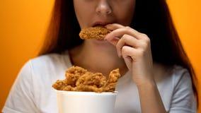Meisje die kippenvleugels, hoog calorievoedsel en gezondheidsrisico's, cholesterol eten stock afbeelding