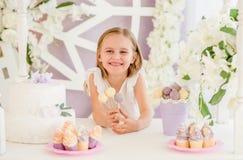 Meisje die kleurrijke zoete lollys in de suikergoedbar houden Stock Foto