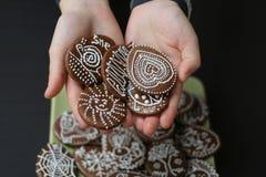 Meisje die koekjes aanbieden (peperkoek) die zij in haar handen houdt Stock Foto