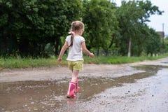Meisje die langs de natte gebroken weg na de regen, platteland lopen stock afbeeldingen