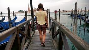 Meisje die in langzame motie op het dek bij gondels in Venetië lopen stock video