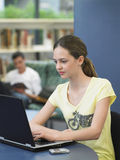 Meisje die Laptop in Bibliotheek met behulp van stock foto's