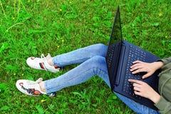 Meisje die laptop buiten op gras met behulp van royalty-vrije stock afbeelding