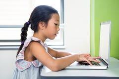 Meisje die Laptop in Klaslokaal met behulp van stock foto