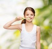 Meisje die in leeg wit overhemd haar tanden borstelen Stock Afbeeldingen