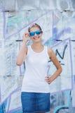 Meisje die lege witte t-shirt, jeans dragen die tegen ruwe straatmuur stellen royalty-vrije stock fotografie