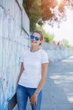 Meisje die lege witte t-shirt, jeans dragen die tegen ruwe straatmuur stellen royalty-vrije stock afbeeldingen
