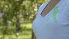 Meisje die lint van de kalk het groene voorlichting op witte t-shirt spelden stock video