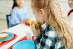 Meisje die lunch hebben op school stock foto's