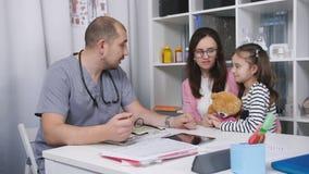 Meisje die mamma en een Teddybeer zenuwachtig in de spreekkamer koesteren Moeder en dochter bij een ontvangst bij stock videobeelden