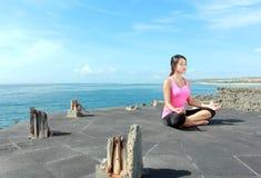 Meisje die meditatie op het strand doen Stock Fotografie
