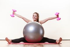 Meisje die met bal en stomme klokgewichten opwarmen stock afbeelding