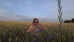 Meisje die met bloemen op een korrelgebied lopen stock video