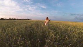 Meisje die met bloemen op een korrelgebied lopen stock videobeelden