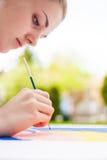 Meisje die met borstel een kunstbeeld schilderen Stock Foto