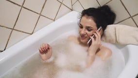 Meisje die met een glimlach op een smartphone spreken die in het bad met schuim liggen stock video