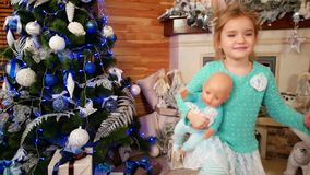 Meisje die met een pop, bobblehead, babypret het vieren Nieuwjaar` s Vooravond dichtbij de Kerstboom, gelukkig weinig dansen stock footage