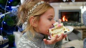 Meisje die met genoegen een brok van cake bij de Kerstboom, Familie door de open haard eten die een dessert met thee eten stock videobeelden