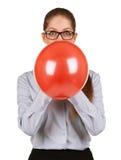 Meisje die een grote rode ballon opblazen royalty-vrije stock fotografie