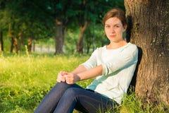 meisje die met grote blauwe ogen in het park in t zitten Royalty-vrije Stock Foto