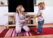 Meisje die met haar peuter binnen broer debatteren over de afstandsbediening Stock Fotografie