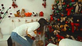 Meisje die met hoofdtelefoons aan muziek het luisteren en zet voorstelt onder de Kerstboom stock videobeelden
