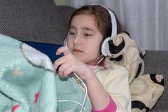 Meisje die met hoofdtelefoons in de telefoon spelen stock afbeeldingen