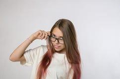 Meisje die met lang haar met glazen de camera en het glimlachen bekijken royalty-vrije stock foto's