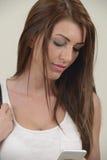 Meisje die met lang haar telefoon bekijken Royalty-vrije Stock Foto's