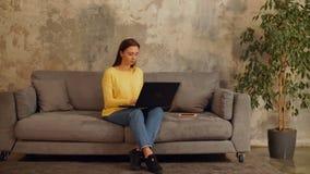 Meisje die met laptop op bank online blog schrijven stock video