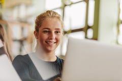 Meisje die met laptop in universitaire klasse bestuderen royalty-vrije stock afbeeldingen