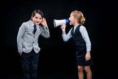 Meisje die met megafoon op jongen schreeuwen stock afbeelding