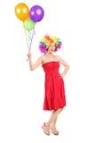 Meisje die met pruik een bos van ballons houden stock foto
