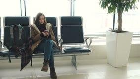Meisje die met smartphone op een vertrek wachten stock footage