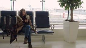 Meisje die met smartphone op het vertrek wachten stock video