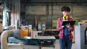 Meisje die met tablet in houten workshop werken die met gadget lopen die rond eruit zien stock video
