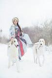 Meisje die met twee windhonden in de winter lopen Stock Foto
