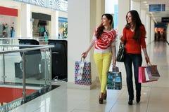 Meisje die met zakken met zijn meisje bij wandelgalerij en het winkelen lopen Royalty-vrije Stock Afbeeldingen