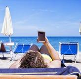 Meisje die mobiele slimme telefoon op een strand met overzees op de achtergrond bekijken voor ontspannings en communicatie concep Stock Afbeeldingen