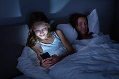 Meisje die Mobiele Telefoon met behulp van terwijl Haar Dochterslaap op Bed royalty-vrije stock foto's