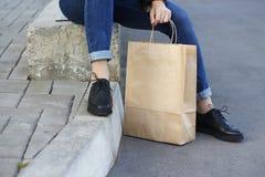 Meisje die in mooie schoenen naast een document zak zitten Royalty-vrije Stock Afbeeldingen