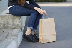 Meisje die in mooie schoenen naast een document zak zitten Stock Afbeelding