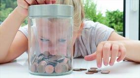 Meisje die muntstukken zetten in een kruik stock videobeelden