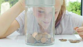 Meisje die muntstukken zetten in een kruik stock video