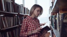 Meisje die naar boek in bibliotheek zoeken stock video