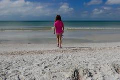 Meisje die naar de oceaan op een wit zandstrand lopen Stock Fotografie