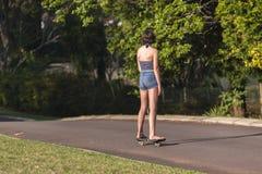 Meisje die naar huis met een skateboard rijden Stock Afbeelding