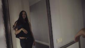Meisje die nieuwe kleren proberen en haar verschijning spiegel bekijken, langzame motielengte stock videobeelden