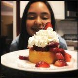 Meisje die omhoog aardbei eyeing shortcake stock afbeeldingen